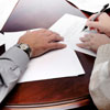 Woman signing a will with the help of an attorney
